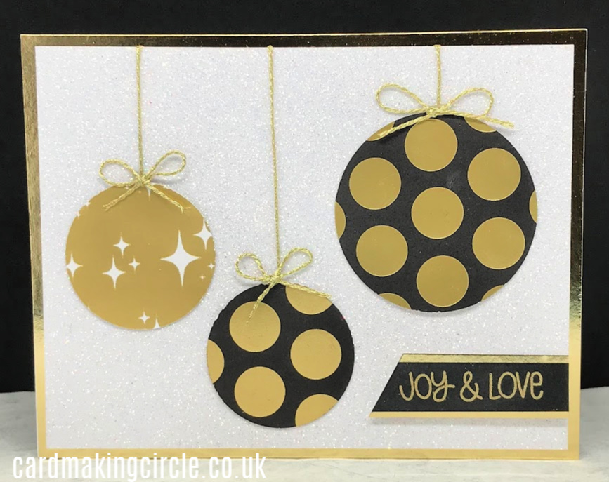 Ornament Christmas card made with die cut circles and gold cord mounted onto glitter paper.