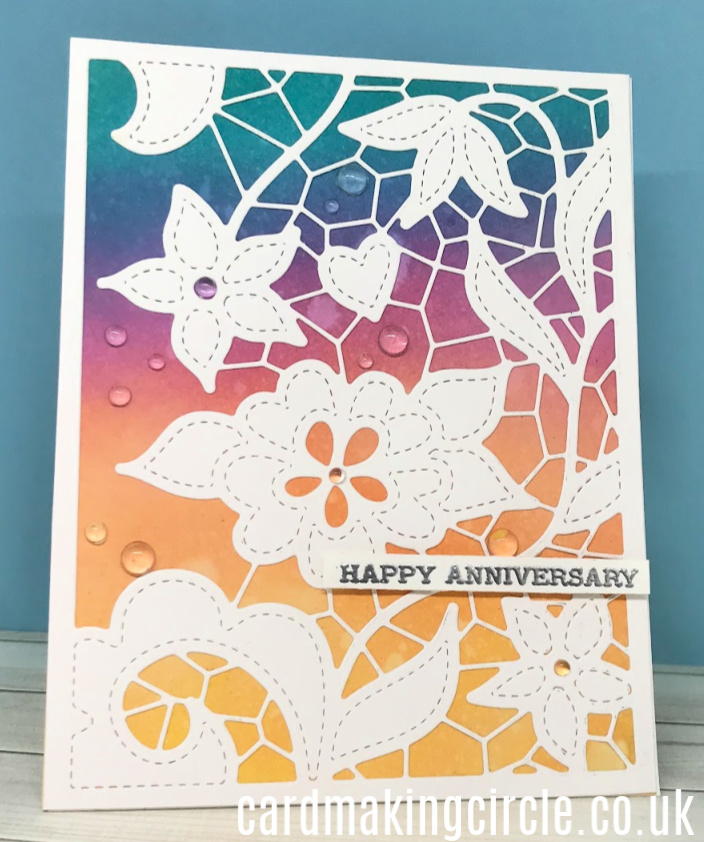 A wedding anniversary card created using distress inks in rainbow order and the doodled lace cover die from Altenew.
