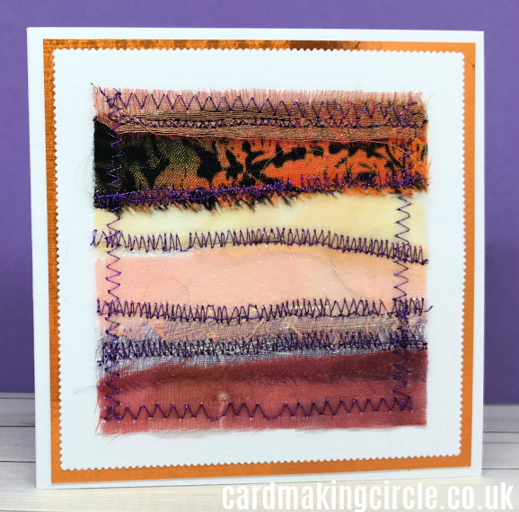 A fabric card made with strips of silk and other materials.