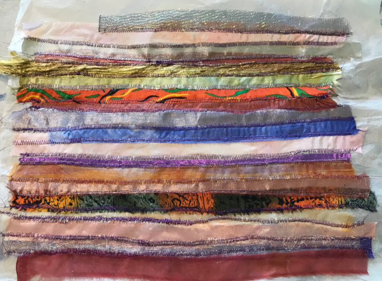 Fabric strips sewn onto transfer adhesive paper.